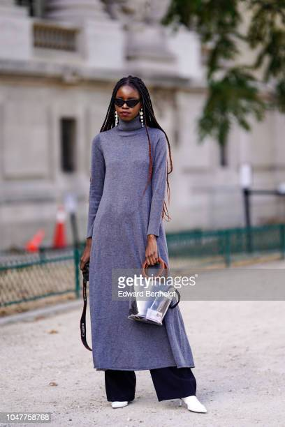 A guest wears a gray turtleneck dress a silver shiny bag flare pants white heels shoes earrings outside Elie Saab during Paris Fashion Week...
