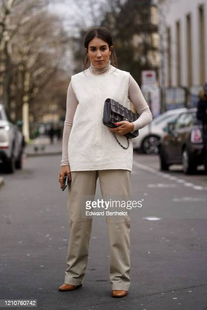 Guest wears a gray turtleneck top, a sleeveless with pullover, gray flared pants, brown leather pointy shoes, a Chanel bag with checked patterns,...