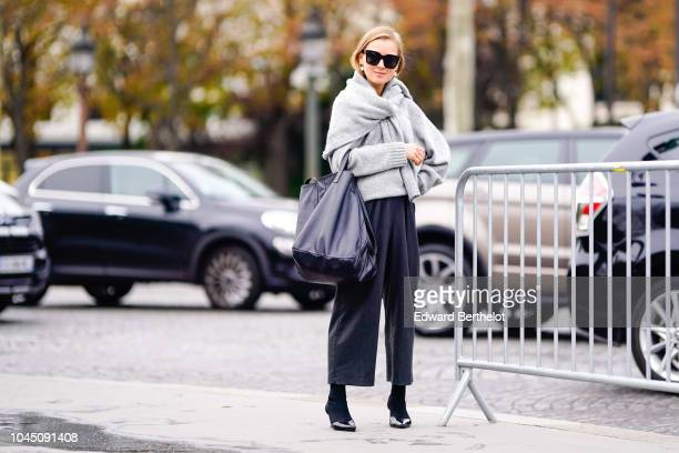 A guest wears a gray wool pullover a black bag black pants outside Chanel during Paris Fashion Week Womenswear Spring/Summer 2019 on October 2 2018...