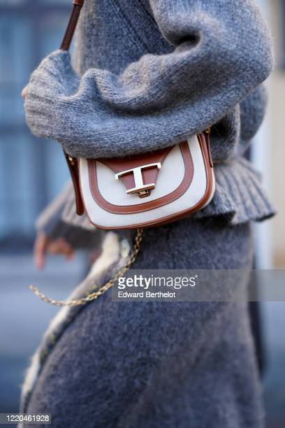 Guest wears a gray wool pullover, a Tod's white and brown leather bag, outside Tod's, during Milan Fashion Week Fall/Winter 2020-2021 on February 21,...