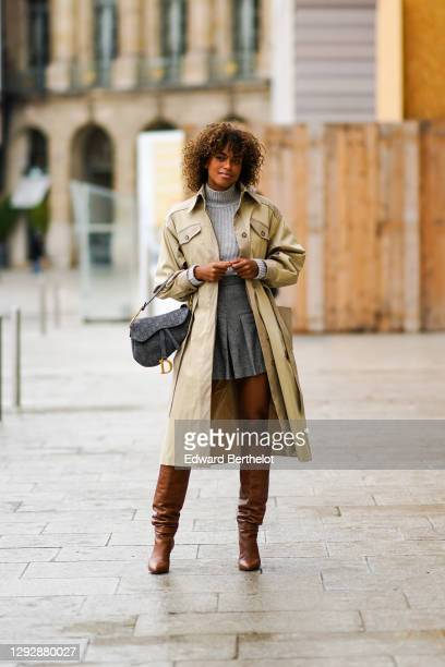 Guest wears a gray wool turtleneck pullover, a beige long trench coat, a gray pleated short skirt, a Dior monogram Saddle bag, brown knee high...
