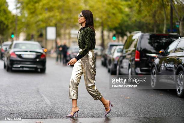 Guest wears a green and black zebra pattern striped pullover, silver shiny cropped pants, purple glitter shoes, sunglasses, outside Miu Miu, during...