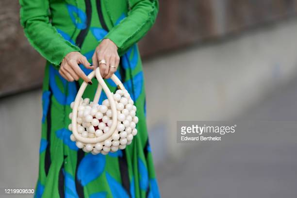 A guest wears a green and blue floral print dress a beaded white bag made of large pearls finger rings outside Marni during Milan Fashion Week...