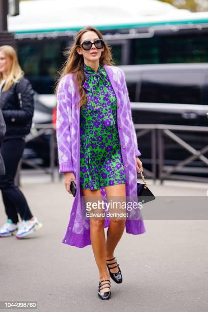 A guest wears a green and purple dress a purple wool jacket black shoes sunglasses outside Miu Miu during Paris Fashion Week Womenswear Spring/Summer...