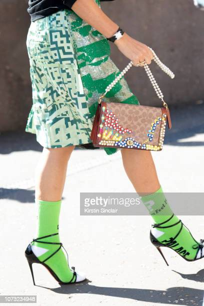 A guest wears a green and white skirt green socks and high heeled sandals during London Fashion Week September 2018 on September 17 2018 in London...