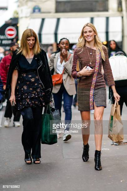 A guest wears a green bag a black jacket a flower print skirt a guest wears a striped sparkly dress black shoes holds a paper bag outside Koche...