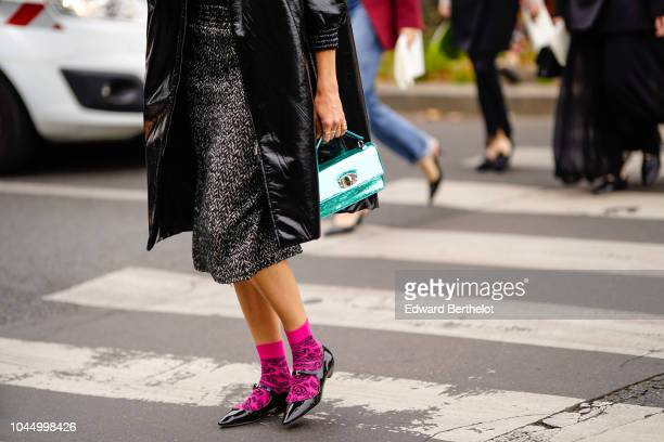 A guest wears a green bag pink socks black shoes outside Miu Miu during Paris Fashion Week Womenswear Spring/Summer 2019 on October 2 2018 in Paris...