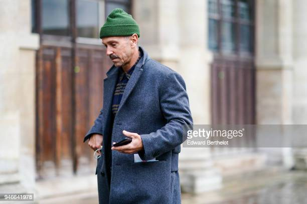 A guest wears a green beanie hat a gray coat a checked shirt outside Thom Browne during Paris Fashion Week Menswear Fall Winter 20182019 on January...