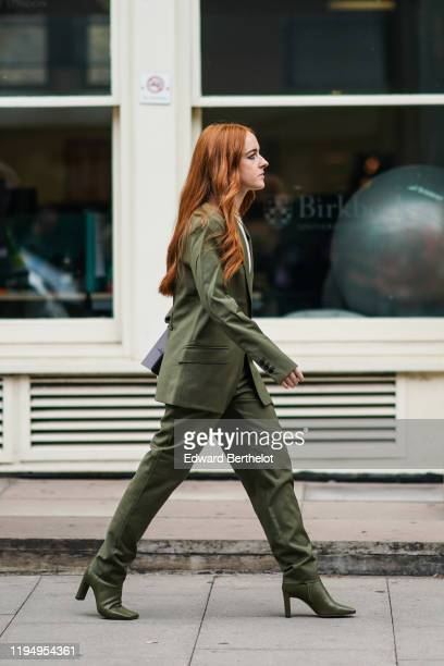 A guest wears a green blazer jacket pants high heeled pointy boots outside JW Anderson during London Fashion Week September 2019 on September 16 2019...