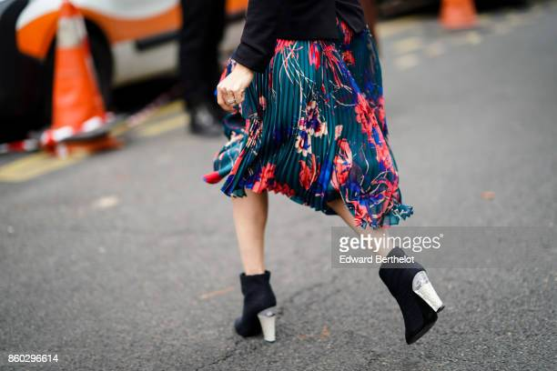 A guest wears a green blue and rose floral print pleated skirt black ankle boots with transparent heels outside Lanvin during Paris Fashion Week...