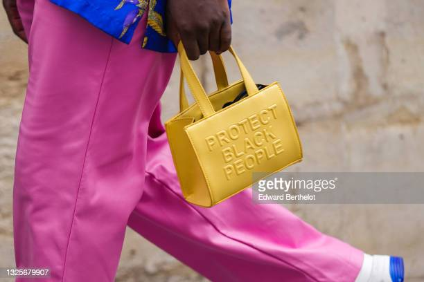Guest wears a green blue with multicolored print pattern shirt, fuchsia pink leather pants, a yellow shiny leather hand bag with an embossed slogan...