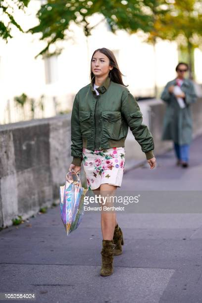A guest wears a green bomber jacket a floral print pink skirt khaki suede boots outside Haider Ackermann during Paris Fashion Week Womenswear...