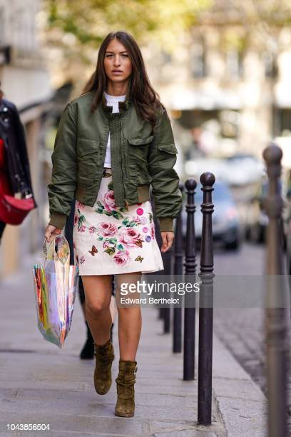 A guest wears a green bomber jacket a pink floral print dress khaki suede shoes outside Altuzarra during Paris Fashion Week Womenswear Spring/Summer...