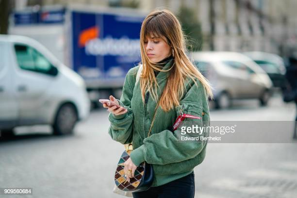 A guest wears a green bomber jacket outside Chanel during Paris Fashion Week Haute Couture Spring/Summer 2018 on January 23 2018 in Paris France