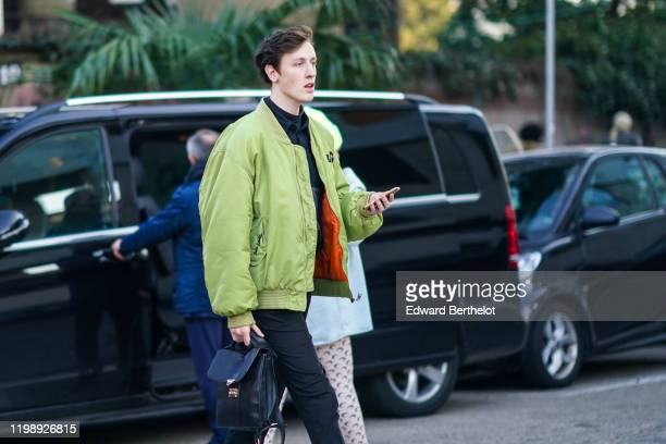 A guest wears a green bomber jacket with orange inner lining a leather bag outside Marni during Milan Fashion Week Fall/Winter 2020/2021 on January...