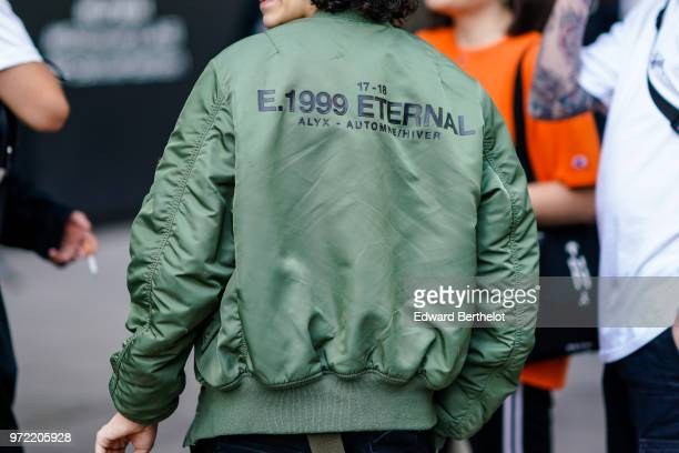 A guest wears a green bomber jacket with printed eternal during London Fashion Week Men's June 2018 on June 09 2018 in London England