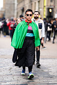Guest wears a green cape a multicolo striped polo shirt a black skirt picture id1091068942?s=170x170