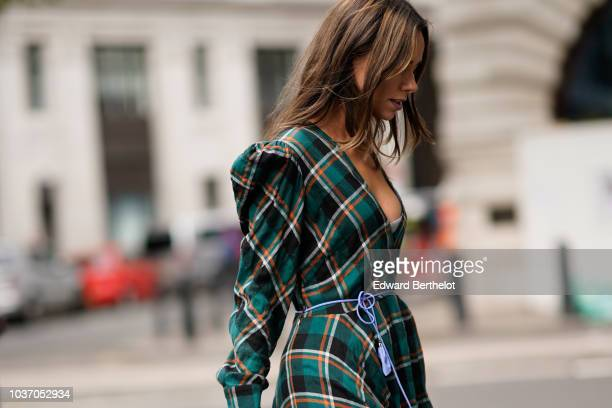 Guest wears a green checked pattern dress, burgundy shoes, during London Fashion Week September 2018 on September 14, 2018 in London, England.