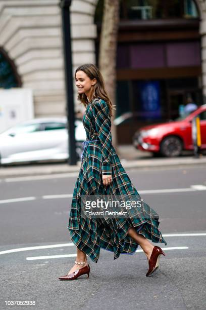 A guest wears a green checked pattern dress burgundy shoes during London Fashion Week September 2018 on September 14 2018 in London England