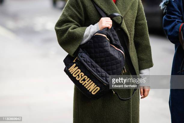 A guest wears a green coat a Moschino black and yellow bag during London Fashion Week February 2019 on February 19 2019 in London England