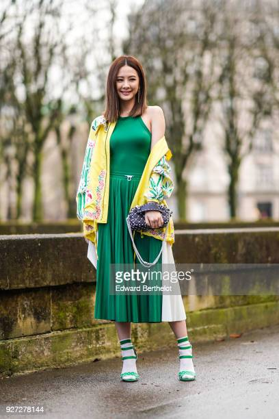 A guest wears a green dress a yellow flower print jacket a studded bag outside Valentino during Paris Fashion Week Womenswear Fall/Winter 2018/2019...