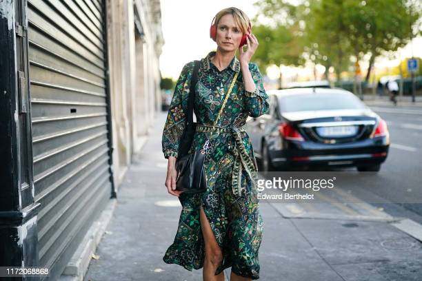 Guest wears a green dress with colorful floral patterns, a black bag, a large black tote bag, outside 24S Launches LVMH Finalists' Collections At...