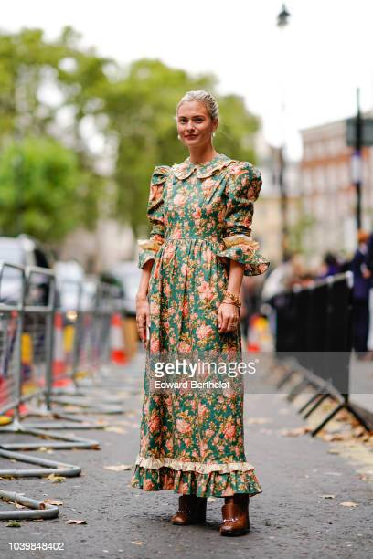 A guest wears a green floral print dress during London Fashion Week September 2018 on September 18 2018 in London England