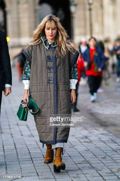 A guest wears a green floral print shirt with white cuffs a navy blue denim trimmed sleeveless brown tweed quilted coat tancolor boots a lustrous...