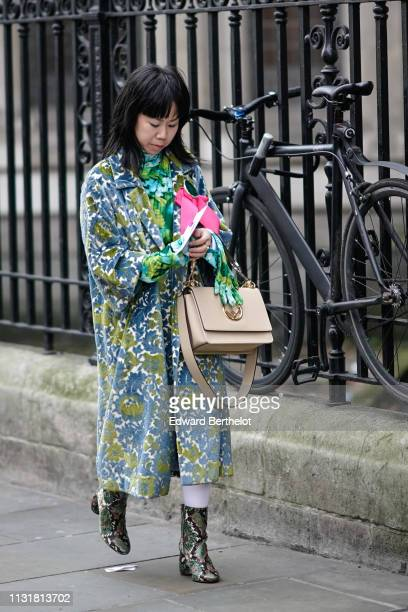 A guest wears a green floral print turtleneck green floral print gloves a green and blue tapestry coat a beige handbag green and brown python pattern...