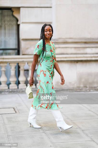 Guest wears a green flowing dress with red floral print, white high heel boots, a bag, during London Fashion Week September 2019 on September 15,...