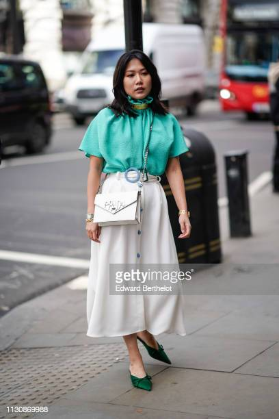 A guest wears a green flowing top a white flowing skirt with a blue round buckle and blue buttons a white Prada bag green pointy mules during London...
