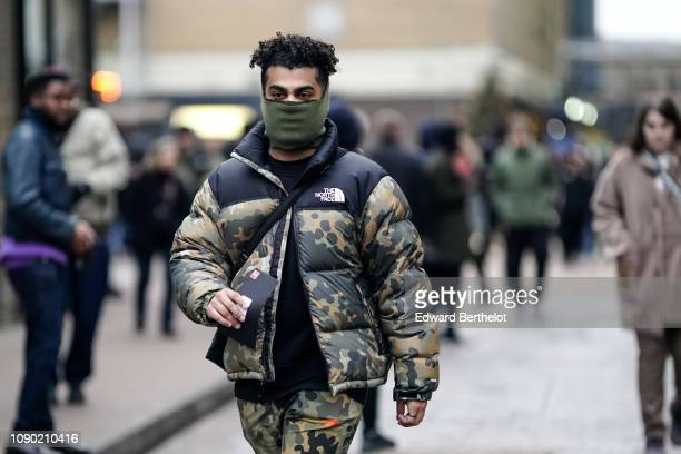 Guest wears a green hood, a military camouflage puffer winter jacket from The North Face, during London Fashion Week Men's January 2019 on January...