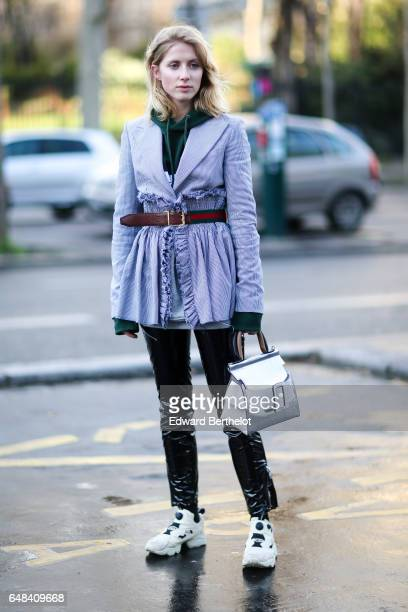A guest wears a green hoodie sweater a striped jacket a Gucci belt black vinyl pants a silver bag and white shoes outside the Mashama show during...