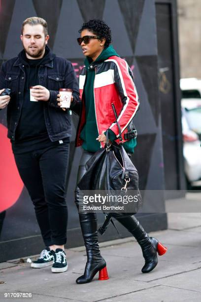 A guest wears a green hoodie sweater sunglasses a black white and red leather jacket a bag black leather thigh high boots with red heels during...