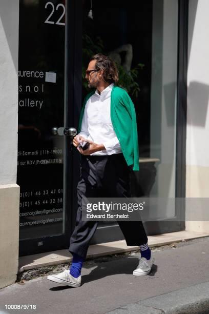 A guest wears a green jacket a white shirt black cropped pants blue socks white sneakers outside Thom Browne during Paris Fashion Week Menswear...
