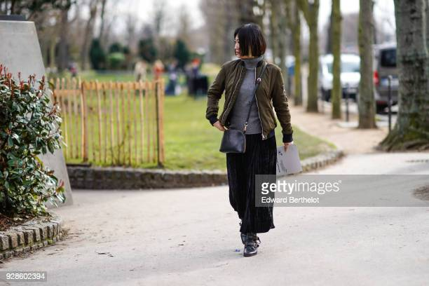 A guest wears a green khaki bomber jacket a gray turtleneck pull over a black skirt black leather shoes outside Beautiful People during Paris Fashion...