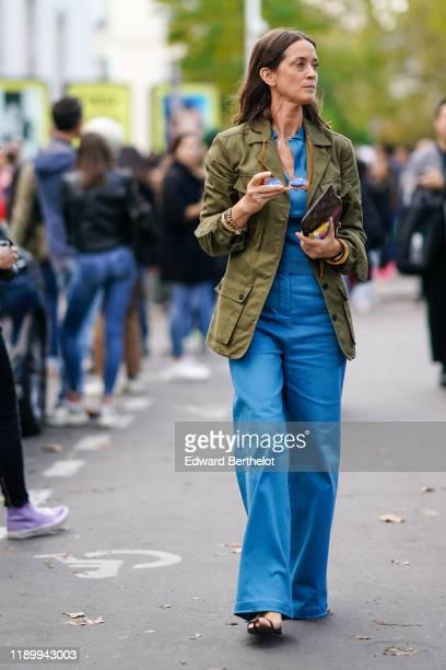 Guest wears a green khaki jacket, a blue top, blue flare pants, outside Nina Ricci, during Paris Fashion Week - Womenswear Spring Summer 2020, on...