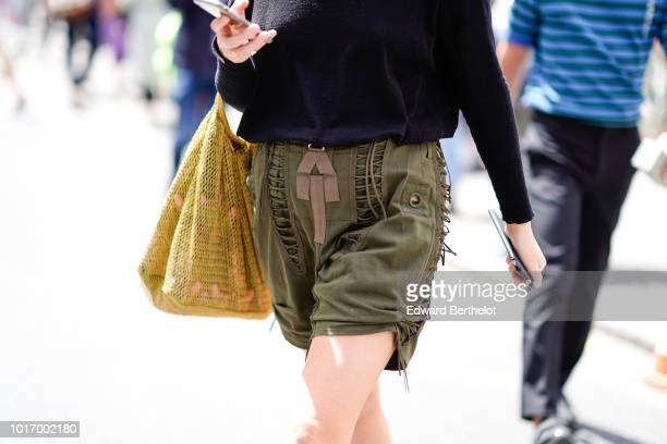 A guest wears a green khaki short a fishnet yellow bag outside Thom Browne during Paris Fashion Week Menswear SpringSummer 2019 on June 23 2018 in...