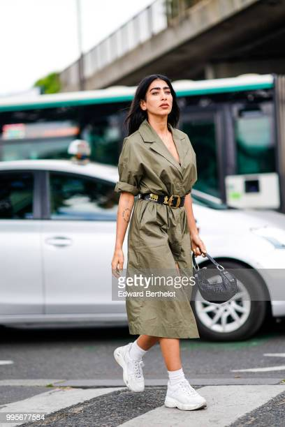 A guest wears a green khaki trench coat dress a black leather belt with golden part white sneakers shoes outside Vetements during Paris Fashion Week...