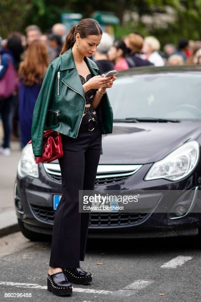 A guest wears a green leather jacket a beige and black open work top black flare pants a red velvet bag platform black studded clogs outside Lanvin...