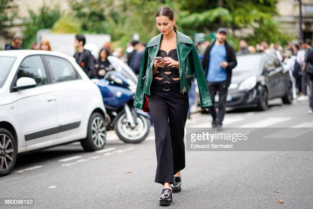 A guest wears a green leather jacket a black and skincolored openwork top black flare pants black platform studded clogs outside Lanvin during Paris...