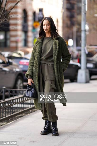 Guest wears a green long fluffy coat, a green khaki t-shirt, green khaki pants, black leather boots, during New York Fashion Week Fall Winter 2020,...
