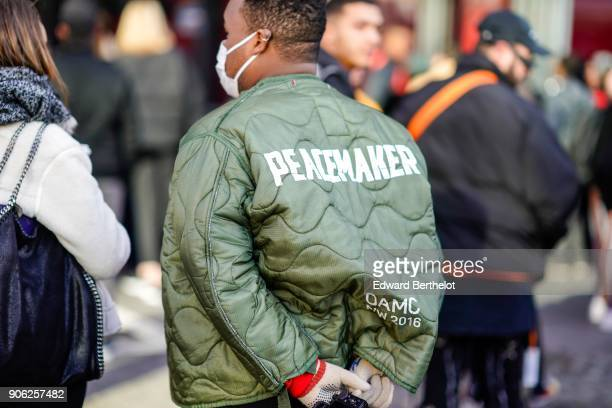 A guest wears a green OAMC Peacemaker bomber jacket outside Off White during Paris Fashion Week Menswear Fall Winter 20182019 on January 17 2018 in...