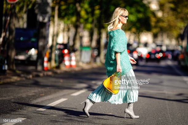 A guest wears a green oversized glitter green top an orange bag a pleated skirt gray heels shoes during Paris Fashion Week Womenswear Spring/Summer...