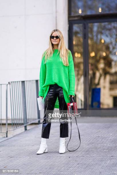 A guest wears a green oversized pull over sunglasses black pvc pants white shoes outside Giambattista Valli during Paris Fashion Week Womenswear...