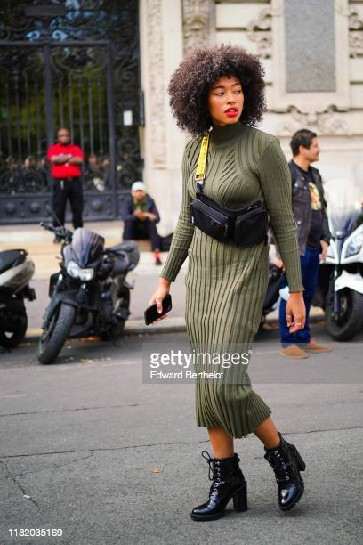 A guest wears a green pleated dress with turtleneck collar black leather shoes a shoulder strapped bag outside Elie Saab during Paris Fashion Week...