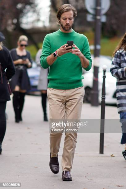 A guest wears a green pull over beige pants brown shoes uses a smartphone to send text messages outside Mugler during Paris Fashion Week Womenswear...