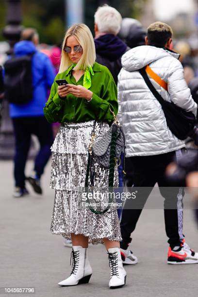 A guest wears a green shirt a flared silver shiny glitter skirt white boots outside Chanel during Paris Fashion Week Womenswear Spring/Summer 2019 on...