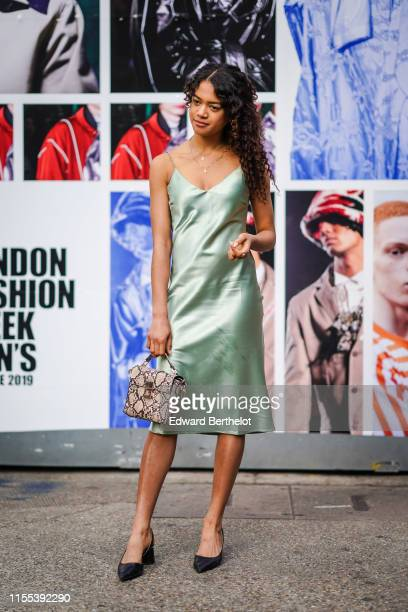 Guest wears a green silk lingerie dress, a python mini bag and black pointy shoes, during London Fashion Week Men's June 2019 on June 09, 2019 in...