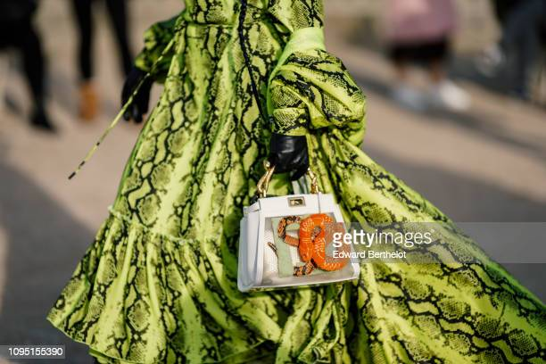 A guest wears a green snake print dress black leather gloves and a snake print bag outside OffWhite during Paris Fashion Week Menswear F/W 20192020...
